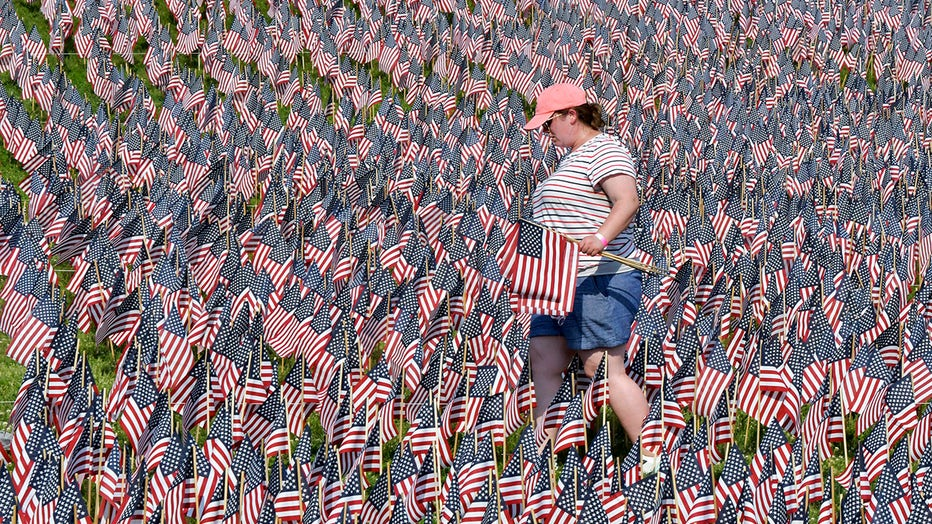 A volunteer wearing a cap, shorts, and T-shirt carries American flags among a sea of flags at Boston Common