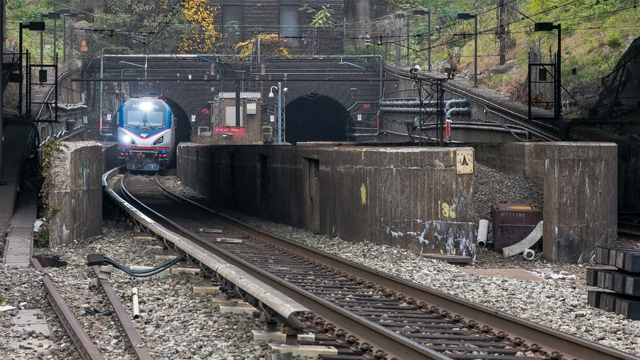 An Amtrak train emerges from a tunnel