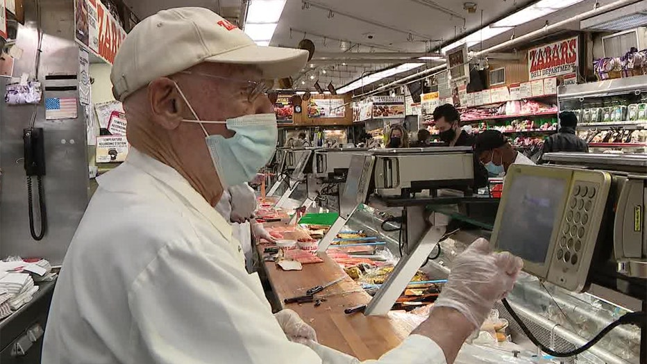 A man wearing a white hat and outfit and blue mask uses a digital panel at a deli counter