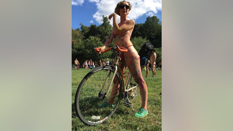 In this Sept. 9, 2017, file photo Olivia Neely, a topless cyclist wearing body paint, motions before the start of that year's annual Philly Naked Bike Ride in Philadelphia. (AP Photo/Dino Hazell, File)