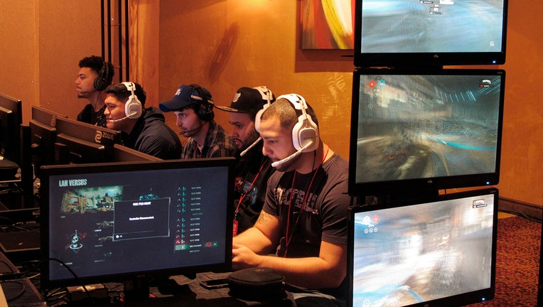 5 gamers wearing headsets sit next to each other as face monitors and play video games inside a casino