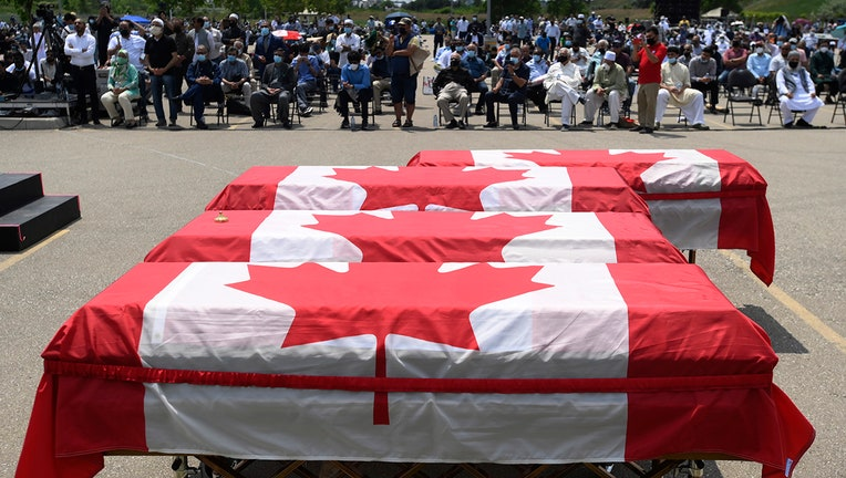 Four caskets are draped with Canadian flags outdoors as dozens of mourners are seen in the background