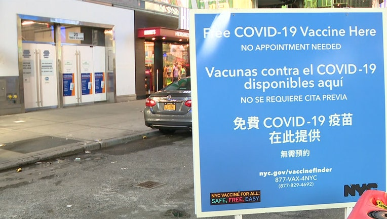 A blue and white sign outside a vaccination site