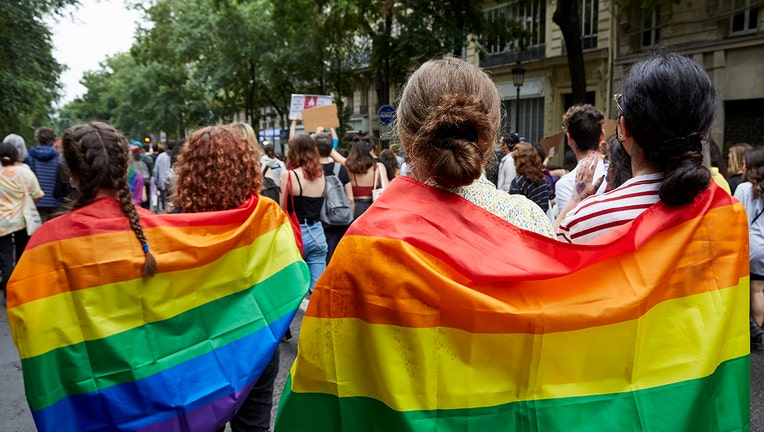 People wearing rainbow flags march in a parade on a tree-lined street in Paris