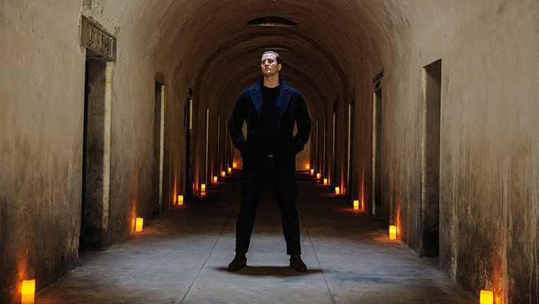 A man in a dark suit stands in a long chamber of catacombs; candles line the chamber