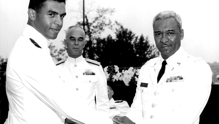 Coast Guard Academy graduate in white uniform shakes hands with his father, an Army colonel in a white uniform, as a Coast Guard admiral stands behind them