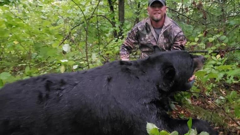 Brett Stimac poses with a bear he shot in September 2019 . (Facebook / Cuyuna Lakes Community Watch)