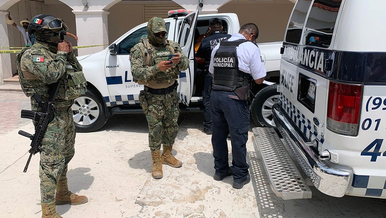 Members of the Mexican Navy are seen outiside of an ambulance carrying a tourist injured during a shooting in the tourist area of Playa Tortugas in Cancun, Mexico on June 11, 2021. -(Photo by ELIZABETH RUIZ/AE/AFP via Getty Images)