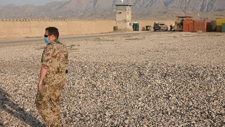 A soldier stands in front of an outer wall of Camp Marmal with a watchtower. (Photo by Michael Fischer/picture alliance via Getty Images)