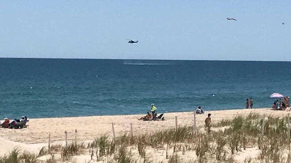 A helicopter searches the waters off 18th Street in Beach Haven, NJ after an aircraft reportedly went down further north off 26th Street in Spray Beach.