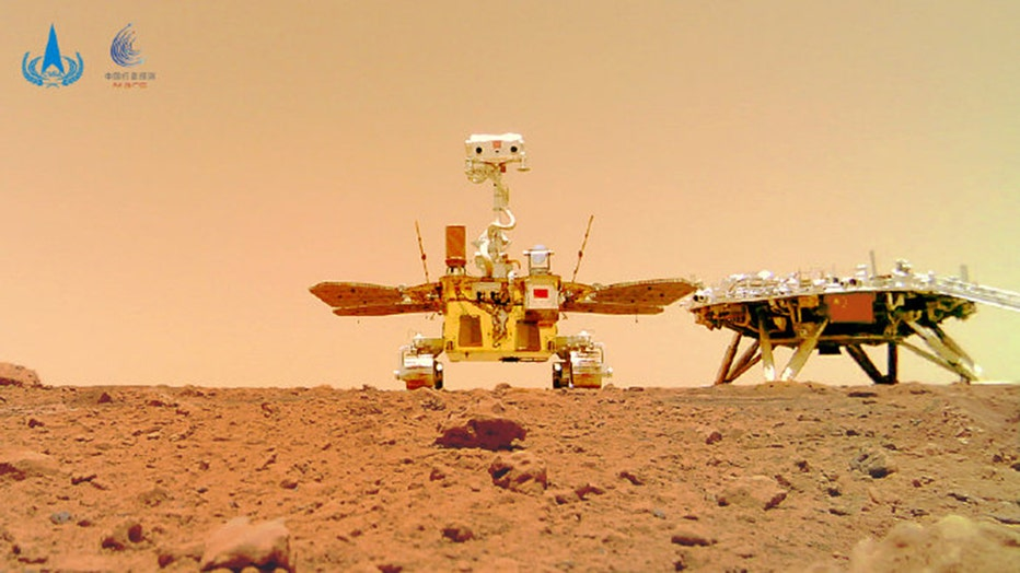 A rover and a landing platform stand on the rocky and dustry surface of Mars