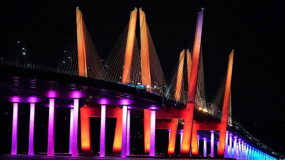 A bridge over the Hudson lit red, orange, yellow, green, blue and violet