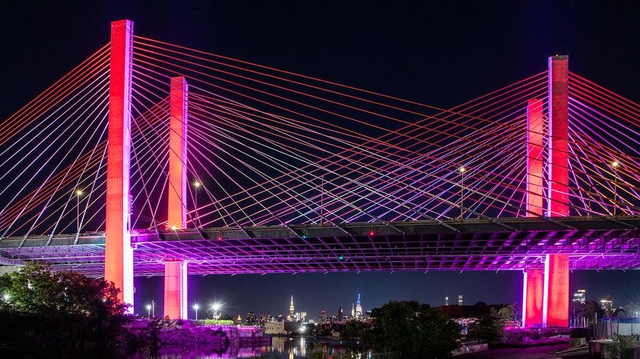 A New York City bridge lit red, orange, yellow, green, blue and violet