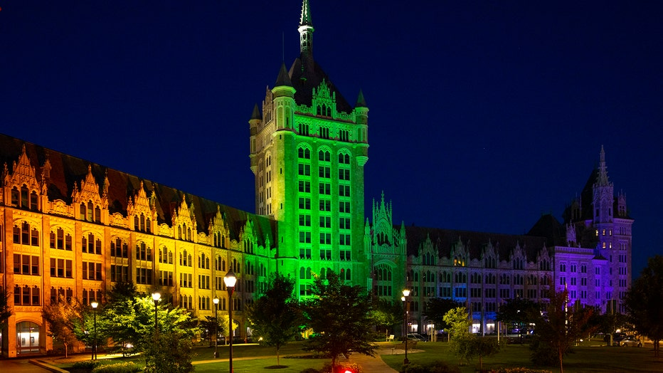 A SUNY building lit red, orange, yellow, green, blue and violet