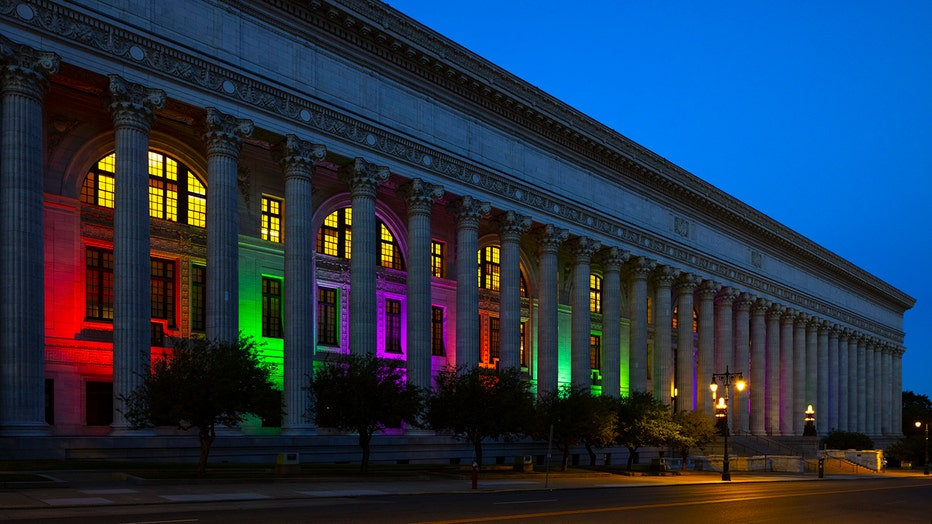 A long building woth columns illuminated for Pride