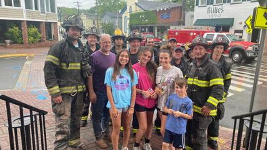 Officials say she was not injured. Photos show her smiling as she poses with the rescuers after the ordeal.