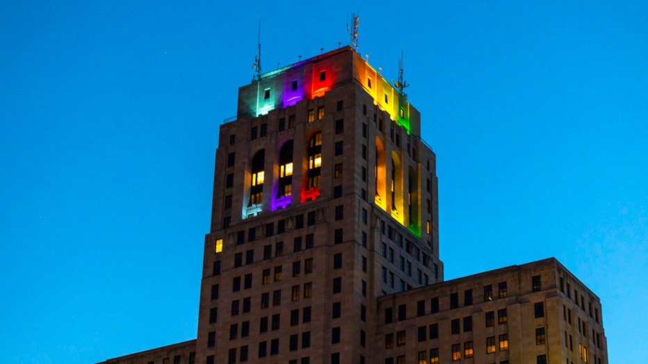 Pride colors illuminate the top of a state office building in Albany