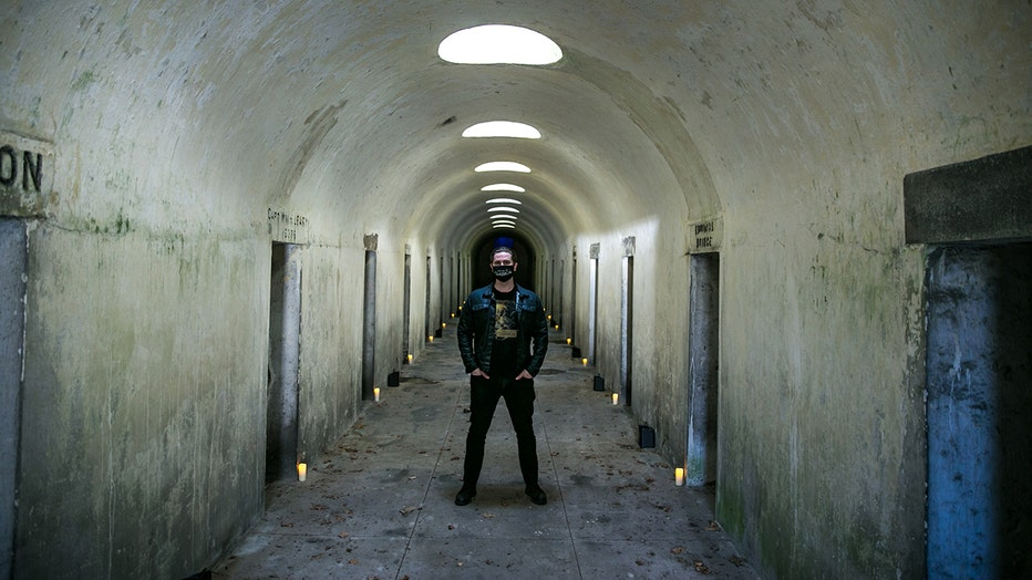 A man wearing a face mask stands in a long chamber of catacombs; candles line the chamber