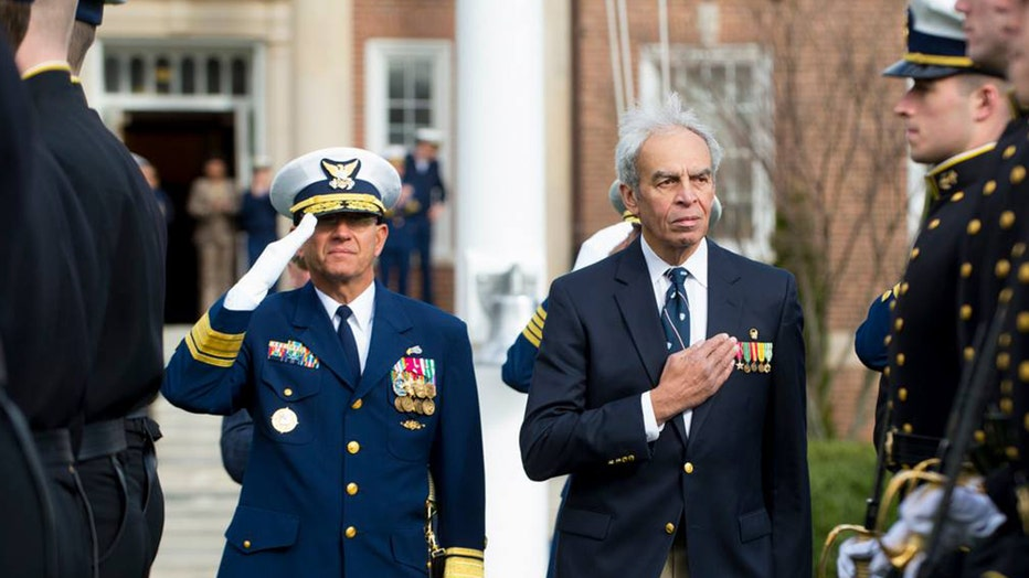 A Coast Guard officer in a blue uniform salutes as a man in a blue suit wearing medals puts his hand over his heart as other Coast Guard personnel stand nearby