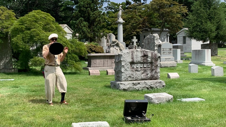 Tour guide wearing period clothes speaks into a vintage megaphone among some graves in a scenic cemetery