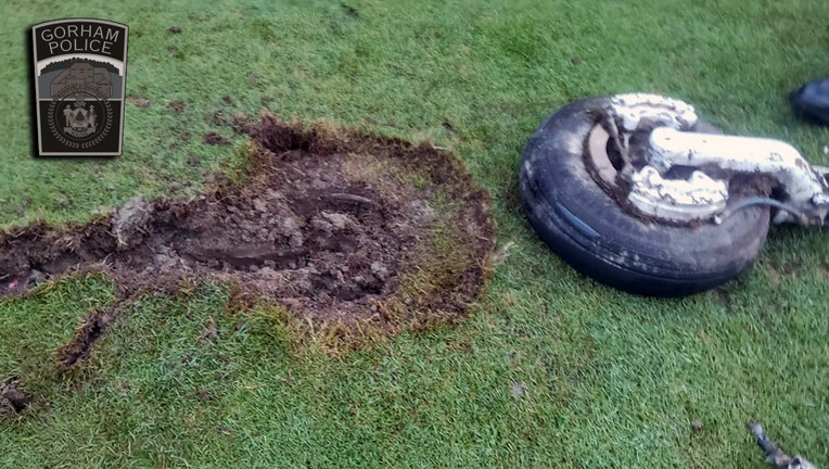 A wheel and strut and the crater it caused in a golf course