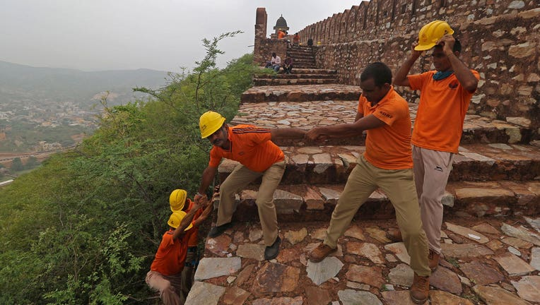 Members of State Disaster Response Force conduct a search operation near the watchtowers of the Amer Fort on the outskirts of Jaipur on July 12, 2021, after at least 11 people were killed in lightning strikes at the fort. (Photo by AFP via Getty Images)