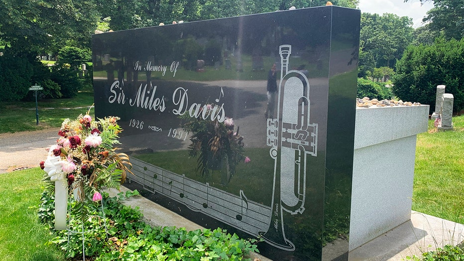 """Closeup of a black headstone etched with the words """"In Memory Of Sir Miles Davis 1926-1991"""""""