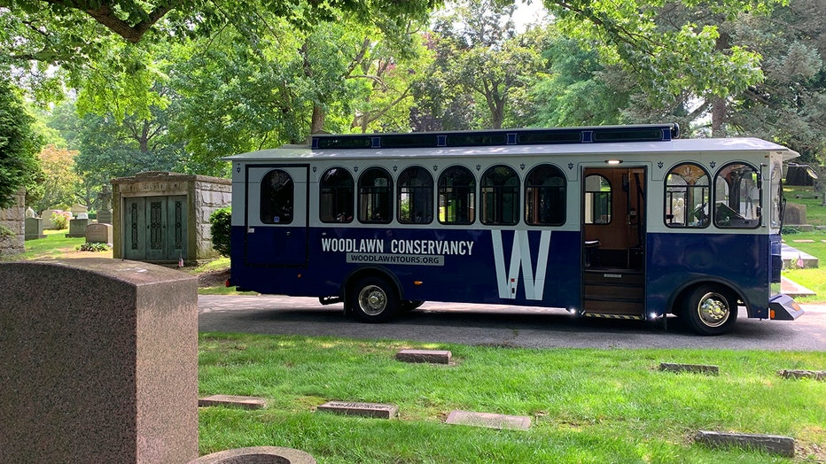 A blue and white bus designed to look like a classic trolley parked along a path in a scenic cemetery