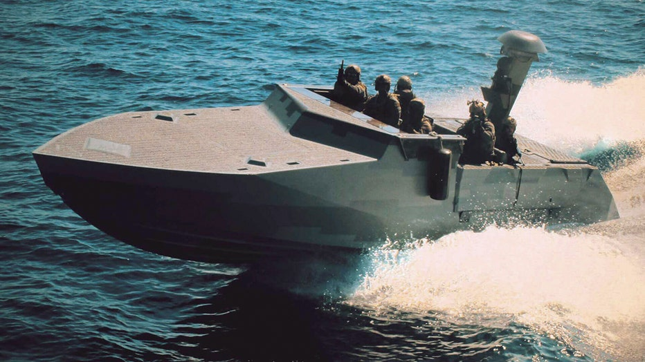 A slate gray navy vessel cuts through the water; several sailors are on board