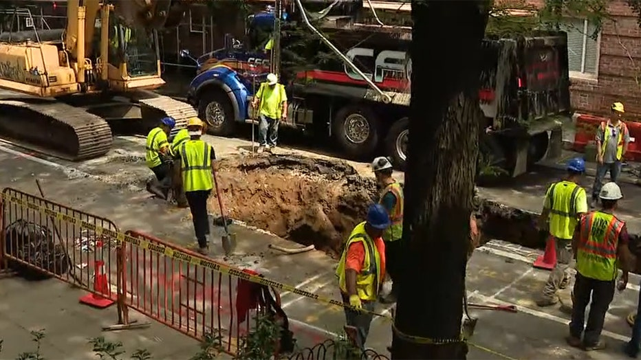 Several workers in hard hats and yellow safety vests work around a large hole in the surface of a tree-lined roadway in Manhattan