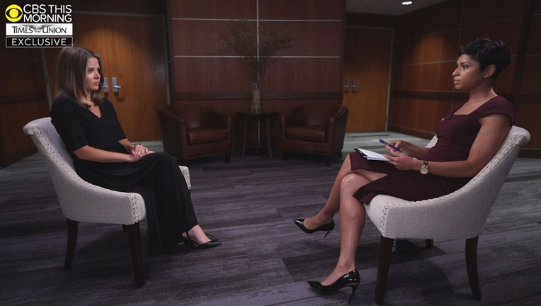 Two women sitting in chairs face each other during an interview