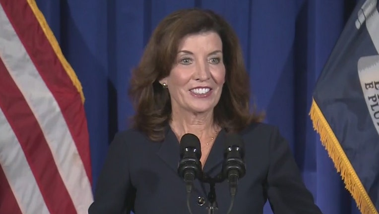 Lt Gov Hochul speaks into two microphones with flags and curtain behind her; she wears a dark suit