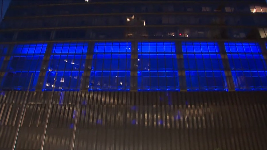 A view of a portion of the facade of a skyscraper with glowing blue lighting