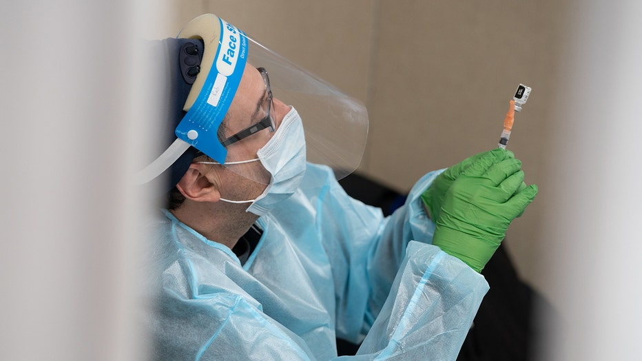 A medical worker wearing green gloves, a light blue mask and gown, and a clear face shield holds up a syringe