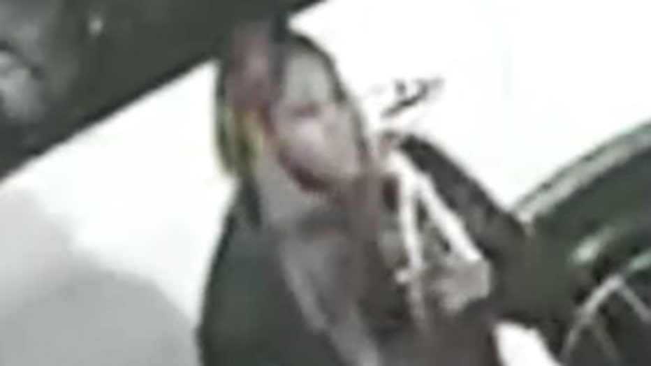 A blurry security camera image showing a person