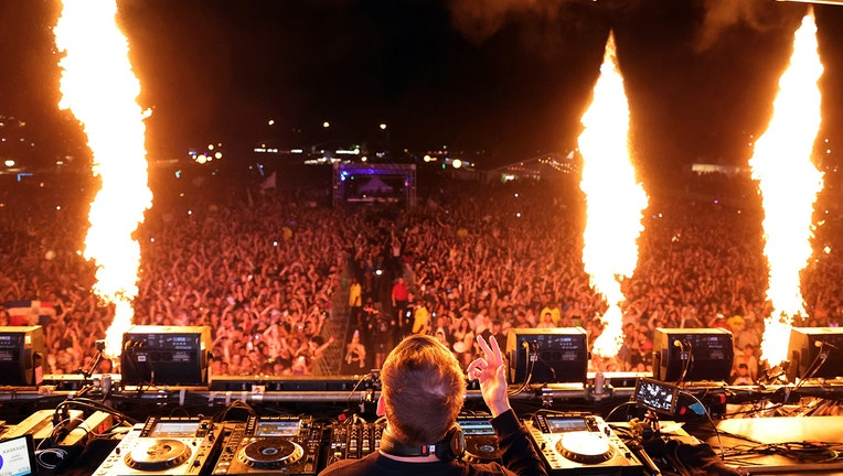 Kaskade performing on stage in front of thousands of fans; pyrotechnics alight