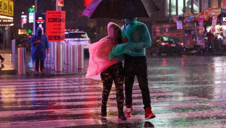 People out in the street during heavy rain and storm at Times Square in New York City, United States on September 1, 2021. (Photo by Tayfun Coskun/Anadolu Agency via Getty Images)