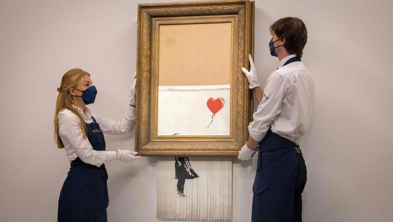 Assistants pose by an artwork titled Love is the Bin by British street artist Banksy during a photocall at Sothebys auction house in central London on September 3, 2021.