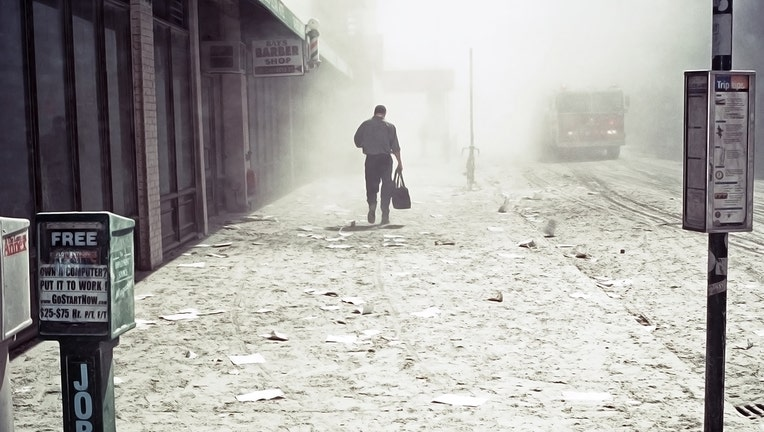 a man walks alone down the deserted sidewalk into the dusty mist; the streets are covered with debris, white dust and ashes from the disaster