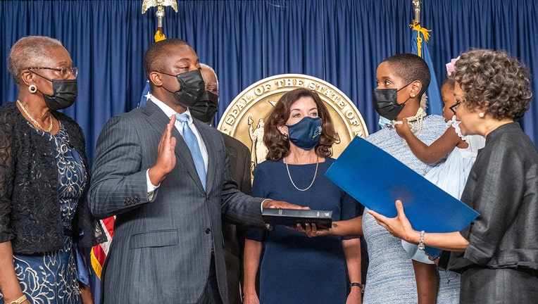 Brian Benjamin is surrounded by family and the governor as he takes the oath of office