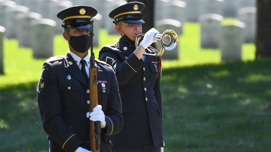 An Honor Guard soldier plays a bugle as another soldier, holding a rifle, stands at attention in a cemetery