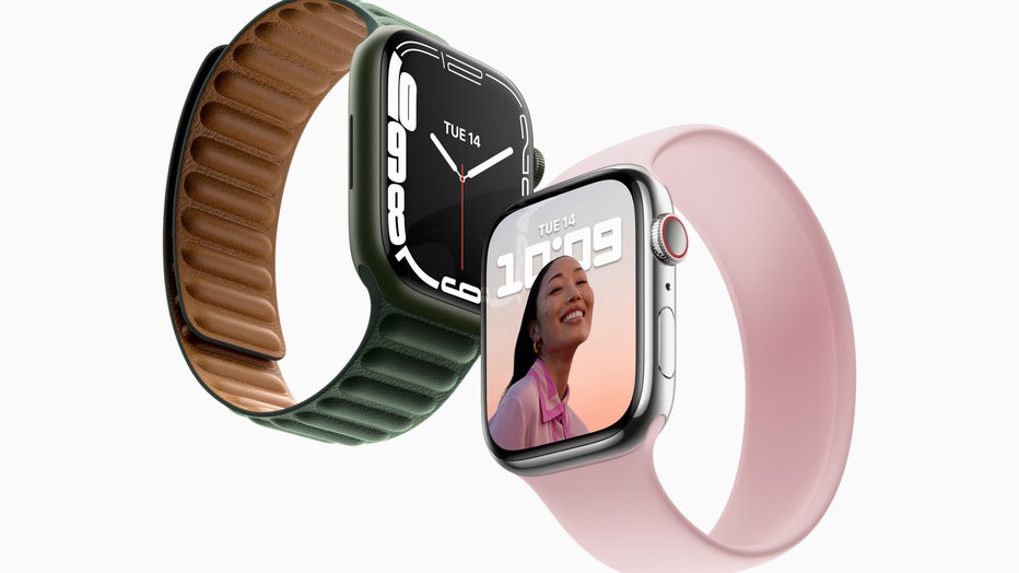 An Apple Watch with a green band and one with a pink band