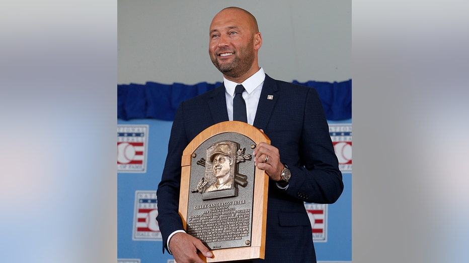 Derek Jeter smiles as he holds his Hall of Fame plaque