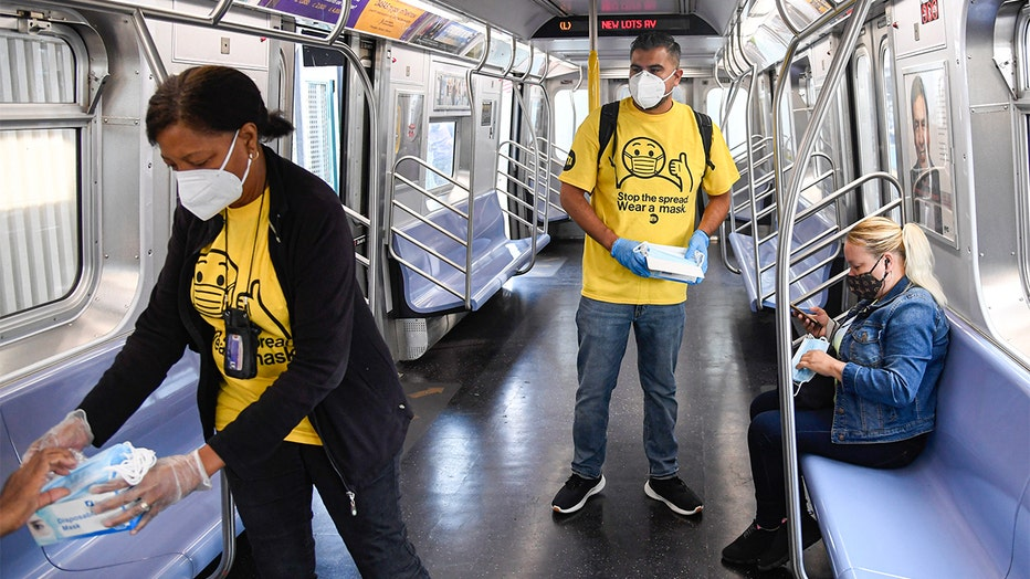 MTA workers wearing white masks and yellow shirts hand out masks to riders in an almost-empty subway car