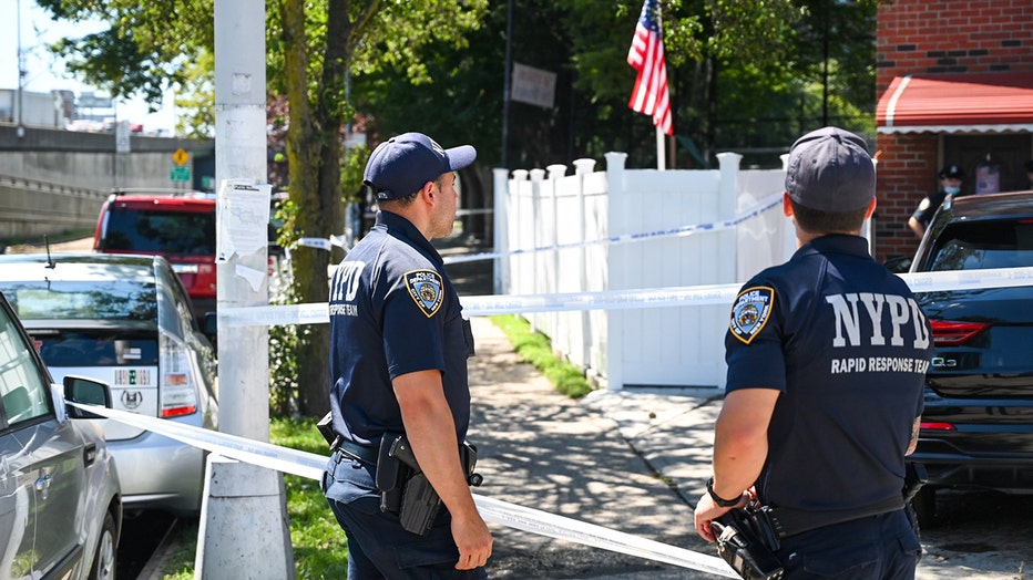 2 officers wearing blue polo shirts and ballcaps stand outside a residence in Queens