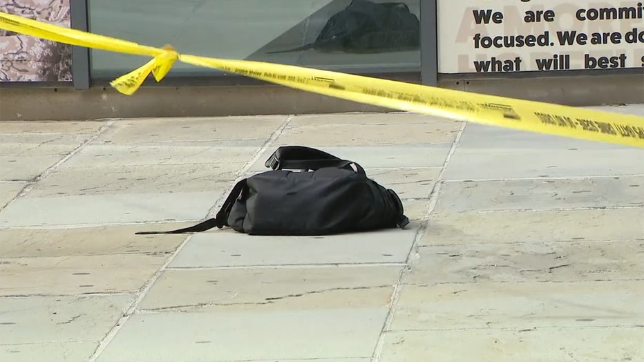 Yellow crime scene tape and a black backpack on the sidewalk