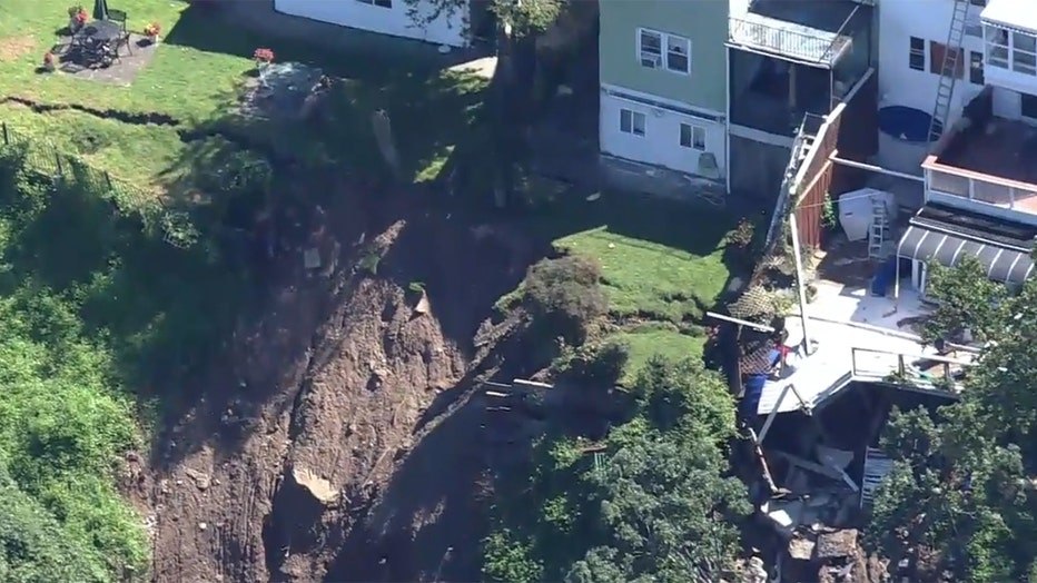 Aerial view of a collapsed deck and a collapsed backyard of suburban homes