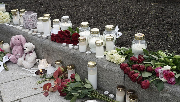 Several bouquets of roses, several candles, and two stuffed animals are left on a sidewalk