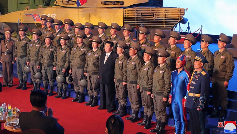 In this photo provided by the North Korean government, North Korean leader Kim Jong Un, center, poses for a group photo with fighter pilots who made the demonstration flight at the opening of an exhibition of weapons systems in Pyongyang, North Korea, Monday, Oct. 11, 2021.(Korean Central News Agency/Korea News Service via AP)