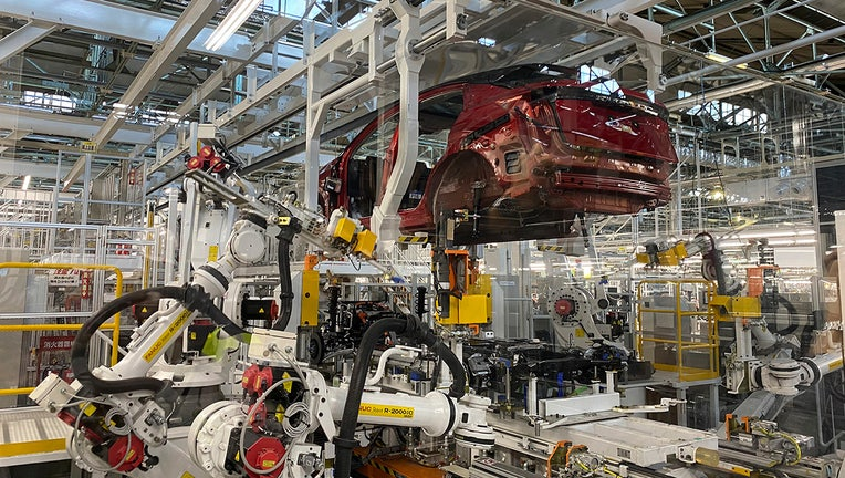 Robotic arms put in the electric vehicle powertrain into the Ariya model in the assembly line at Nissan's Tochigi plant in Kaminokawa town, Tochigi prefecture, Japan, Friday, Oct. 8, 2021. (AP Photo/Yuri Kageyama)